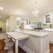 Crystal chandeliers, modern crystal-look stools, and shiny brass cabinetry, countertop, cuisine classique, estate, home, interior design, kitchen, property, real estate, room, gray