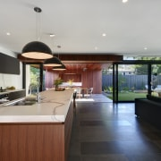 Large stacker doors connect a wood-lined outdoor dining architecture, countertop, estate, house, interior design, kitchen, real estate, window, gray