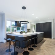 The stepped island cabinetry and countertop together accommodate architecture, chair, floor, furniture, house, interior design, product design, table, white