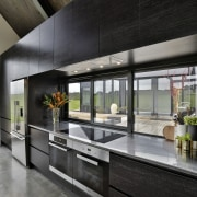 Carlielle Kitchens created this semi-industrial kitchen with recessed countertop, interior design, lobby, black, gray