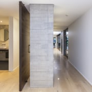 This textured concrete dividing wall has a pivot apartment, architecture, floor, flooring, home, house, interior design, loft, real estate, wood, wood flooring, gray, white