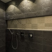 The custom Italian porcelain tile inset in this architecture, bathroom, darkness, floor, flooring, interior design, light, public toilet, reflection, room, texture, tile, wall, black