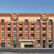 Built in 1922, the Dalgety Wool Stores is apartment, architecture, brick, building, commercial building, condominium, elevation, facade, home, landmark, mixed use, neighbourhood, property, real estate, residential area, window, teal