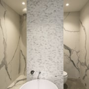 Contrasting the large-format perimeter wall panels, tiny Alarti bathroom, ceiling, floor, flooring, interior design, plumbing fixture, product design, room, tap, tile, wall, white