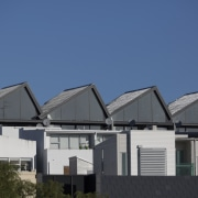 The saw-tooth roof on Scanlan Lofts apartments echoes architecture, building, facade, home, house, property, real estate, residential area, roof, sky, suburb, blue
