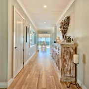 Indoor cricket anyone? A long circulation corridor is apartment, ceiling, estate, floor, flooring, hardwood, home, interior design, property, real estate, room, wood, orange