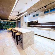 This marble island has a waterfall countertop with countertop, floor, flooring, interior design, kitchen, real estate, gray
