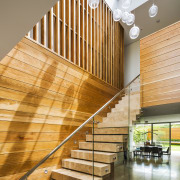A timber front door provides an early touch apartment, architecture, daylighting, handrail, home, interior design, lobby, real estate, stairs, wood, orange, brown