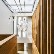The double-height entry hall to this home includes architecture, ceiling, daylighting, handrail, house, interior design, stairs, wood, white, brown