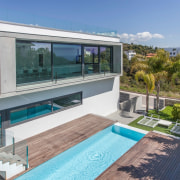 A long pool runs parallel to the main house, property, real estate, swimming pool, villa, window, gray, teal