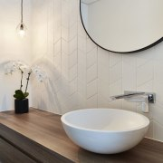 A large circular mirror sits above the sink bathroom, bathroom sink, ceramic, floor, flooring, interior design, plumbing fixture, product design, sink, tap, tile, toilet seat, gray