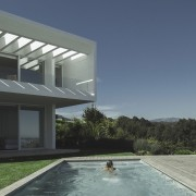 The pool sits disconnected from the main home architecture, estate, home, house, property, real estate, residential area, swimming pool, villa, window, gray, blue