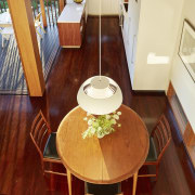 A small U kitchen makes the most of chair, dining room, floor, flooring, furniture, hardwood, home, interior design, laminate flooring, living room, room, table, wood, wood flooring, red