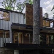 The deck wraps around this tree architecture, building, elevation, facade, home, house, property, real estate, residential area, siding, black, gray