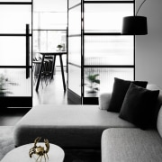 Glass doors and walls help to light the angle, black and white, coffee table, floor, furniture, home, house, interior design, living room, monochrome, monochrome photography, product design, table, wall, white, black