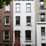 Outside, the home blends into its neighbours apartment, architecture, building, door, facade, home, house, neighbourhood, property, real estate, residential area, window, white