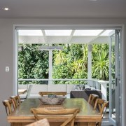 The dining area opens to forest views and ceiling, home, house, interior design, living room, table, window, gray