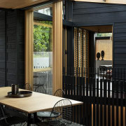This central kitchen and accompanying dining area follows architecture, home, house, interior design, patio, porch, window, wood, black