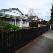 From the street, it's hard to imagine there's cottage, facade, fence, home, house, neighbourhood, plant, property, real estate, residential area, road, tree, walkway, black