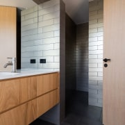 The bathroom is spacious and features contrasting elements architecture, bathroom, ceiling, floor, flooring, interior design, room, sink, tile, wall, wood flooring, gray, black