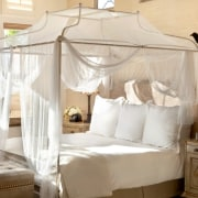 Fine fittings line the bedrooms bed, bed frame, bedroom, four poster, furniture, home, interior design, mosquito net, product, suite, white