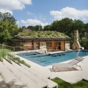 The pool house appears to emerge from the estate, home, house, leisure, property, real estate, resort, swimming pool, villa, white, brown