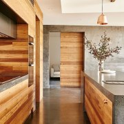 Concrete countertops and wood cabinets and drawers are architecture, cabinetry, ceiling, countertop, floor, flooring, hardwood, home, interior design, laminate flooring, lobby, real estate, wall, wood, wood flooring, wood stain, brown, white, orange