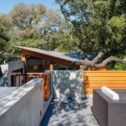 Wood, concrete and glass define this this home architecture, backyard, home, house, outdoor structure, plant, property, real estate, roof, tree, wood, gray