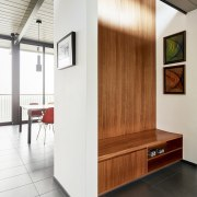 A seating area in the entrance provides a architecture, floor, flooring, furniture, interior design, wall, white