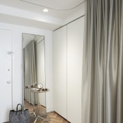 Storage cupboards sit next to the front door. ceiling, curtain, door, floor, flooring, furniture, interior design, room, textile, wall, wardrobe, window, window covering, window treatment, gray