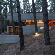 The home is partly nestled into the hillside cottage, home, house, log cabin, tree, wood, black