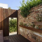The garden during the day architecture, deck, house, outdoor structure, property, real estate, wall, wood, brown, black