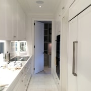 A long, narrow kitchen features ample work space countertop, floor, interior design, kitchen, property, real estate, room, gray