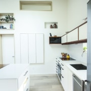 Clever storage spaces line the living area countertop, daylighting, floor, home, house, interior design, kitchen, room, white, gray