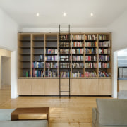 A large bookshelf separates the hallway and living bookcase, furniture, interior design, living room, property, real estate, shelf, shelving, gray