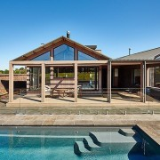 A luxurious pool sits just outside the outdoor cottage, estate, home, house, outdoor structure, property, real estate, swimming pool, villa, teal