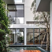 The home appears to be mostly glass from architecture, building, condominium, courtyard, facade, home, house, interior design, real estate, residential area, gray, black