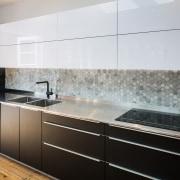 Hexagonal tiles make up the long splashback cabinetry, countertop, floor, interior design, kitchen, product design, gray, black, white