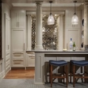 Tucked in next to the staircase, this small cabinetry, countertop, cuisine classique, floor, furniture, interior design, kitchen, room, gray, black