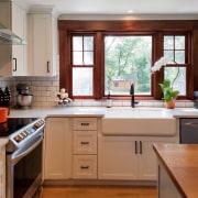 A substantial sink sits below a set of cabinetry, countertop, cuisine classique, floor, flooring, hardwood, home, interior design, kitchen, real estate, room, window, brown