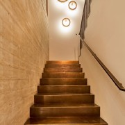 A staircase with bronze stairs and a concrete handrail, interior design, lighting, stairs, orange, brown