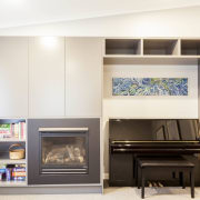 A piano, fireplace and bookshelf sit alongside one furniture, interior design, room, shelving, white