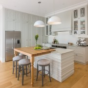 A small 'table' hangs out from the island cabinetry, countertop, cuisine classique, floor, flooring, furniture, hardwood, interior design, kitchen, laminate flooring, table, wood flooring, gray