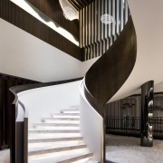 A curving staircase with recessed lighting takes you architecture, building, daylighting, handrail, house, interior design, product design, stairs, black, gray