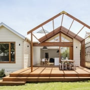 A large outdoor space transitions to the lawn backyard, cottage, deck, estate, facade, home, house, outdoor structure, property, real estate, roof, white, brown