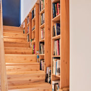 A bookshelf integrated into the stairway wall bookcase, floor, flooring, furniture, hardwood, home, shelf, shelving, stairs, wood, orange, white