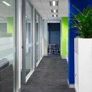 This hallway receives plenty of natural light thanks floor, flooring, interior design, office, gray