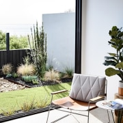 The living room opens out to a small backyard, chair, furniture, home, house, interior design, living room, outdoor furniture, patio, plant, shade, table, window, white