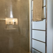 A large shower rail sits outside the shower bathroom, daylighting, floor, flooring, glass, interior design, plumbing fixture, room, tile, wall, brown