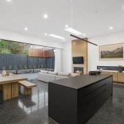 The black island rises up out of the architecture, countertop, house, interior design, kitchen, real estate, gray